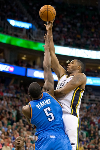 Oct 30, 2013; Salt Lake City, UT, USA; Utah Jazz power forward Derrick Favors (15) goes up for a shot over Oklahoma City Thunder center Kendrick Perkins (5) during the second half at EnergySolutions Arena. Oklahoma City won 101-98. Mandatory Credit: Russ Isabella-USA TODAY Sports