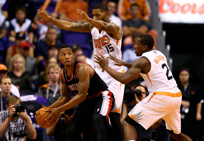 Oct 30, 2013; Phoenix, AZ, USA; Portland Trail Blazers guard Damian Lillard (left) controls the ball against Phoenix Suns guard Eric Bledsoe (2) and Marcus Morris (15) in the second half at US Airways Center. The Suns defeated the Blazers 104-91. Mandatory Credit: Mark J. Rebilas-USA TODAY Sports