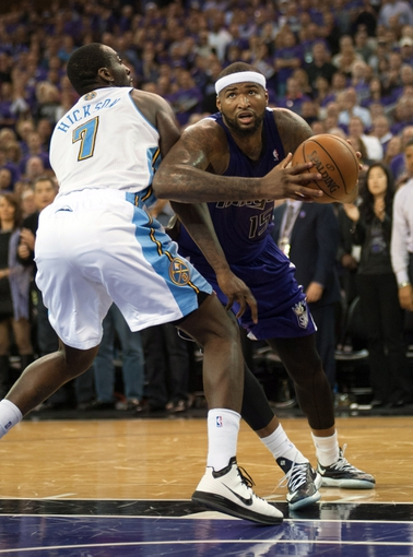 Oct 30, 2013; Sacramento, CA, USA; Sacramento Kings center DeMarcus Cousins (15) drives to the basket against Denver Nuggets power forward J.J. Hickson (7) during the fourth quarter at Sleep Train Arena. The Sacramento Kings defeated the Denver Nuggets 90-88. Mandatory Credit: Ed Szczepanski-USA TODAY Sports