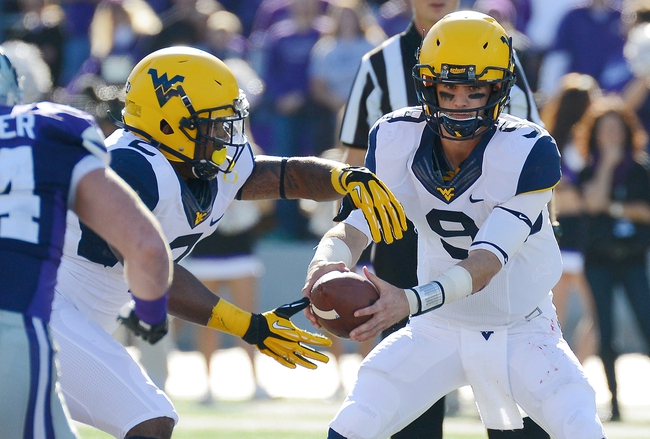 Oct 26, 2013; Manhattan, KS, USA; West Virginia Mountaineers quarterback Clint Trickett (9) hands the ball off to running back Dreamius Smith (2) against the West Virginia Mountaineers during the first half at Bill Snyder Family Stadium. Mandatory Credit: Jasen Vinlove-USA TODAY Sports