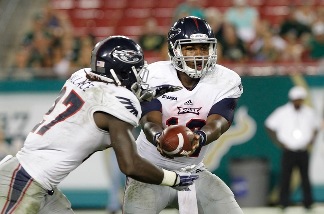 Sep 14, 2013; Tampa, FL, USA; Florida Atlantic Owls quarterback Jaquez Johnson (12) hand the ball off to running back Jonathan Wallace (27) during the second quarter against the South Florida Bulls at Raymond James Stadium. Florida Atlantic Owls defeated the South Florida Bulls 28-10. Mandatory Credit: Kim Klement-USA TODAY Sports