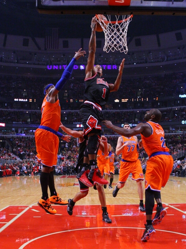 Oct 31, 2013; Chicago, IL, USA; Chicago Bulls point guard Derrick Rose (center) scores past New York Knicks small forward Carmelo Anthony (left) and point guard Raymond Felton (right) during the second half at the United Center. Chicago won 82-81. Mandatory Credit: Dennis Wierzbicki-USA TODAY Sports