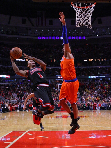 Oct 31, 2013; Chicago, IL, USA; Chicago Bulls point guard Derrick Rose (1) shoots over New York Knicks center Tyson Chandler (6) during the second half at the United Center. Chicago won 82-81. Mandatory Credit: Dennis Wierzbicki-USA TODAY Sports