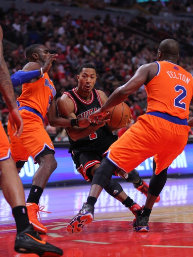 Oct 31, 2013; Chicago, IL, USA; Chicago Bulls point guard Derrick Rose (center) drives between New York Knicks shooting guard Tim Hardaway Jr. (left) and point guard Raymond Felton (2) during the second half at the United Center. Chicago won 82-81. Mandatory Credit: Dennis Wierzbicki-USA TODAY Sports