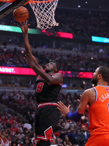 Oct 31, 2013; Chicago, IL, USA; Chicago Bulls small forward Luol Deng (9) scores past New York Knicks center Tyson Chandler (6) during the second half at the United Center. Chicago won 82-81. Mandatory Credit: Dennis Wierzbicki-USA TODAY Sports