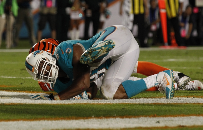Oct 31, 2013; Miami Gardens, FL, USA; Miami Dolphins defensive end Cameron Wake (91) sacks Cincinnati Bengals quarterback Andy Dalton (hidden) in the end zone for a safety in overtime at Sun Life Stadium.  Miami won 22-20. Mandatory Credit: Robert Mayer-USA TODAY Sports