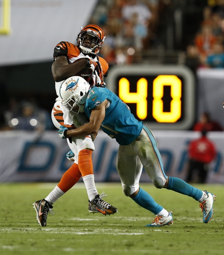 Oct 31, 2013; Miami Gardens, FL, USA;  Cincinnati Bengals wide receiver Mohamed Sanu (12) is tackled by Miami Dolphins cornerback Brent Grimes (21) in the second half at Sun Life Stadium.  Miami won 22-20. Mandatory Credit: Robert Mayer-USA TODAY Sports