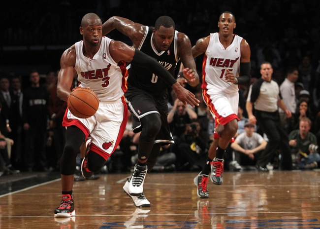 Nov 1, 2013; Brooklyn, NY, USA; Miami Heat shooting guard Dwyane Wade (3) leads a break past Brooklyn Nets center Andray Blatche (0) during the second quarter of a game at Barclays Center. Mandatory Credit: Brad Penner-USA TODAY Sports