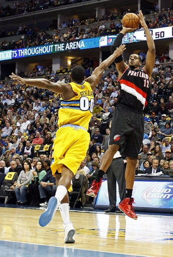 Nov 1, 2013; Denver, CO, USA; Denver Nuggets power forward Darrell Arthur (00) tries to guard Portland Trail Blazers power forward LaMarcus Aldridge (12) before he gets a shot off in the second quarter at the Pepsi Center. Mandatory Credit: Isaiah J. Downing-USA TODAY Sports