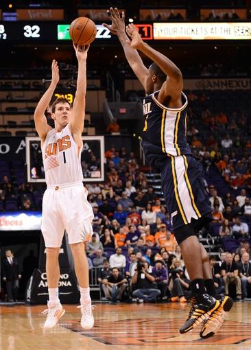 Nov 1, 2013; Phoenix, AZ, USA; Phoenix Suns guard Goran Dragic (1) puts up a shot against the Utah Jazz forward Derrick Favors (15) in the first half at US Airways Center. Mandatory Credit: Jennifer Stewart-USA TODAY Sports