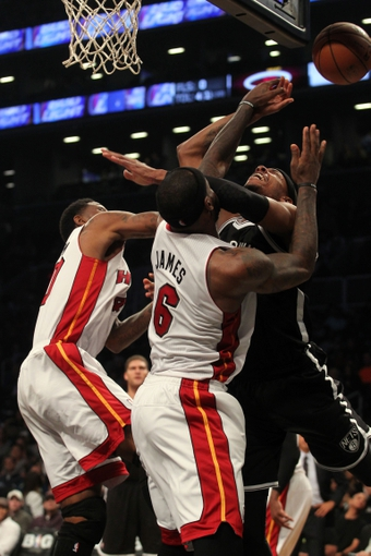 Nov 1, 2013; Brooklyn, NY, USA; Brooklyn Nets small forward Paul Pierce (34) goes up for a shot against Miami Heat small forward LeBron James (6) and Miami Heat power forward Udonis Haslem (40) during the third quarter of a game at Barclays Center. Mandatory Credit: Brad Penner-USA TODAY Sports