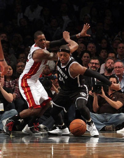 Nov 1, 2013; Brooklyn, NY, USA; Miami Heat point guard Mario Chalmers (15) and Brooklyn Nets small forward Paul Pierce (34) chase the ball during the fourth quarter of a game at Barclays Center. Mandatory Credit: Brad Penner-USA TODAY Sports