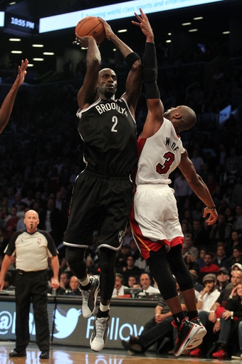Nov 1, 2013; Brooklyn, NY, USA; Brooklyn Nets power forward Kevin Garnett (2) shoots over Miami Heat shooting guard Dwyane Wade (3) during the fourth quarter of a game at Barclays Center. Mandatory Credit: Brad Penner-USA TODAY Sports