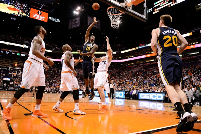Nov 1, 2013; Phoenix, AZ, USA; Utah Jazz forward Derrick Favors (15) lays up the ball against the Phoenix Suns forward P.J Tucker (17) and forward Miles Plumlee (22) in the second half at US Airways Center.  The Suns defeated the Jazz 87-84. Mandatory Credit: Jennifer Stewart-USA TODAY Sports
