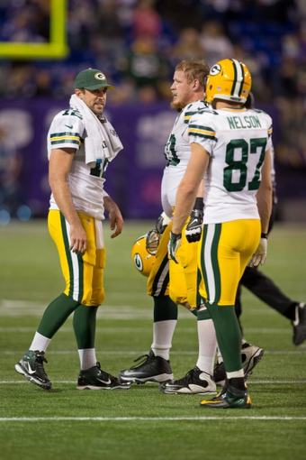 Oct 27, 2013; Minneapolis, MN, USA; Green Bay Packers quarterback Aaron Rodgers (12) congratulates guard T.J. Lang (70) and wide receiver Jordy Nelson (87) after the Packers kicked a field goal against the Minnesota Vikings in the fourth quarter at Mall of America Field at H.H.H. Metrodome. The Packers win 44-31. Mandatory Credit: Bruce Kluckhohn-USA TODAY Sports