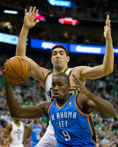 Oct 30, 2013; Salt Lake City, UT, USA; Oklahoma City Thunder power forward Serge Ibaka (9) is defended by Utah Jazz center Enes Kanter (0) during the first half at EnergySolutions Arena. Oklahoma City won 101-98. Mandatory Credit: Russ Isabella-USA TODAY Sports