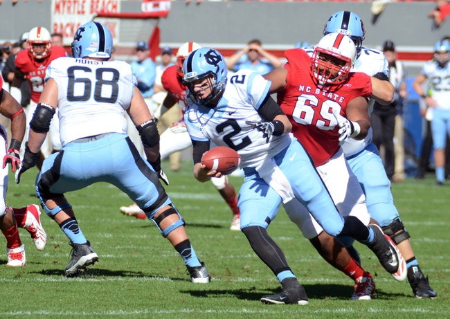 Nov 2, 2013; Raleigh, NC, USA; North Carolina Tar Heels quarterback Bryn Renner (2) rolls out of the pocket as he is pressured by North Carolina State Wolfpack defensive tackle Thomas Teal (69) at Carter Finley Stadium. Mandatory Credit: Rob Kinnan-USA TODAY Sports