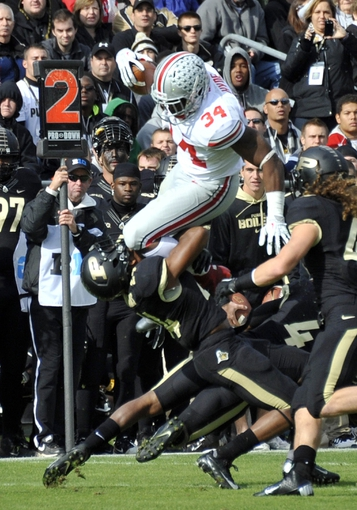 Nov 2, 2013; West Lafayette, IN, USA;  Ohio State Buckeyes running back Carlos Hyde (34) leaps over Purdue Boilermakers defensive back Frankie Williams (24) in the first half at Ross Ade Stadium. Mandatory Credit: Sandra Dukes-USA TODAY Sports