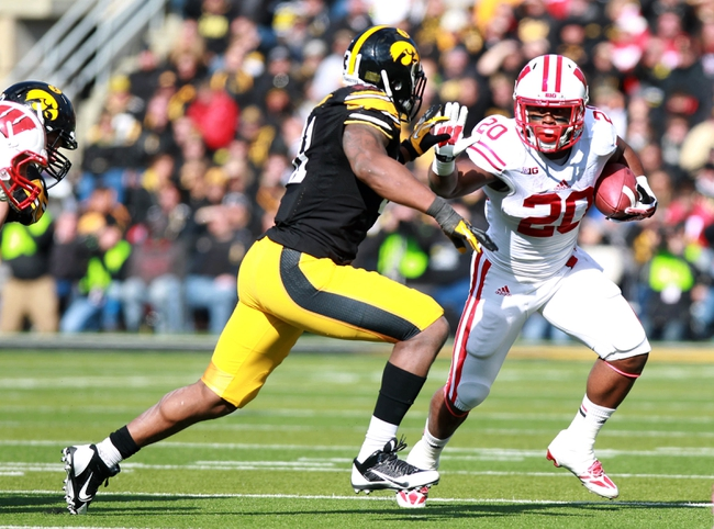 Nov 2, 2013; Iowa City, IA, USA; Wisconsin Badgers running back James White (20) tries to escape Iowa Hawkeyes linebacker Anthony Hitchens (31) at Kinnick Stadium. Mandatory Credit: Reese Strickland-USA TODAY Sports
