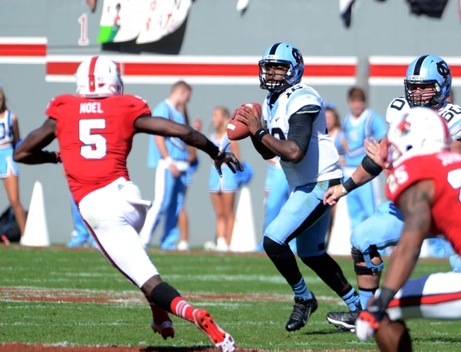 Nov 2, 2013; Raleigh, NC, USA; North Carolina Tar Heels quarterback Marquise Williams (12) looks to throw as North Carolina State Wolfpack linebacker Rodman Noel (5) defends during the first half at Carter Finley Stadium. Mandatory Credit: Rob Kinnan-USA TODAY Sports