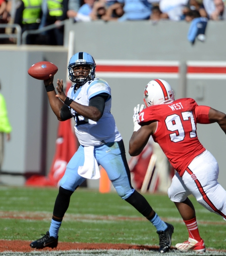 Nov 2, 2013; Raleigh, NC, USA; North Carolina Tar Heels quarterback Marquise Williams (12) throws as he is pressured by North Carolina State Wolfpack defensive end Forrest West (97) during the first half at Carter Finley Stadium. Mandatory Credit: Rob Kinnan-USA TODAY Sports
