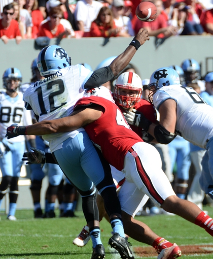 Nov 2, 2013; Raleigh, NC, USA; North Carolina Tar Heels quarterback Marquise Williams (12) is hit as he throws by North Carolina State Wolfpack linebacker Robert Caldwell (48) during the first half at Carter Finley Stadium. Mandatory Credit: Rob Kinnan-USA TODAY Sports