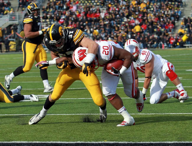 Nov 2, 2013; Iowa City, IA, USA;  Wisconsin Badgers running back James White (20) is tackled by the Iowa Hawkeyes safety John Lowdermilk (37) at Kinnick Stadium.  Wisconsin beat Iowa 28-9.  Mandatory Credit: Reese Strickland-USA TODAY Sports