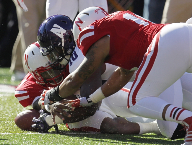 Nov 2, 2013; Lincoln, NE, USA; Nebraska Cornhuskers quarterback Tommy Armstrong Jr. (4) recovers a fumble against teammate Cethan Carter (11) and Northwestern Wildcats player Treveon Henry (10) at Memorial Stadium. Mandatory Credit: Bruce Thorson-USA TODAY Sports
