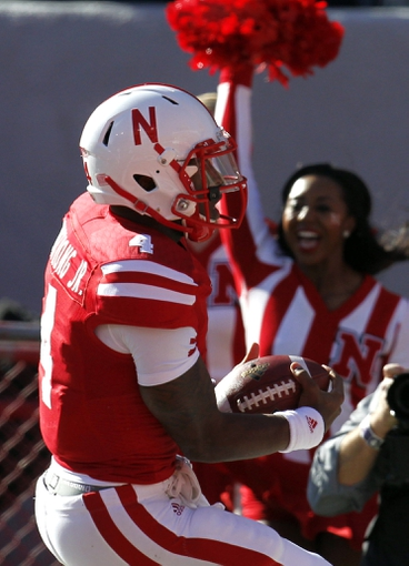 Nov 2, 2013; Lincoln, NE, USA; Nebraska Cornhuskers quarterback Tommy Armstrong Jr. (4) scores a touchdown against the Northwestern Wildcats at Memorial Stadium. Mandatory Credit: Bruce Thorson-USA TODAY Sports