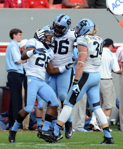 Nov 2, 2013; Raleigh, NC, USA;  at Carter Finley Stadium.  North Carolina Tar Heels defensive back Brian Walker(28) celebrates a fourth quarter interception against the North Carolina State Wolfpack with teammates Ethan Farmer (96) and Jeff Schoettmer (34). North Carolina beat North Carolina State 27-19.  Mandatory Credit: Rob Kinnan-USA TODAY Sports
