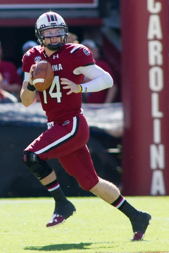 Nov 2, 2013; Columbia, SC, USA; South Carolina Gamecocks quarterback Connor Shaw (14) rolls out of the pocket during the first half against the Mississippi State Bulldogs at Williams-Brice Stadium. The Gamecocks defeated the Bulldogs 34-16.  Mandatory Credit: Jeremy Brevard-USA TODAY Sports