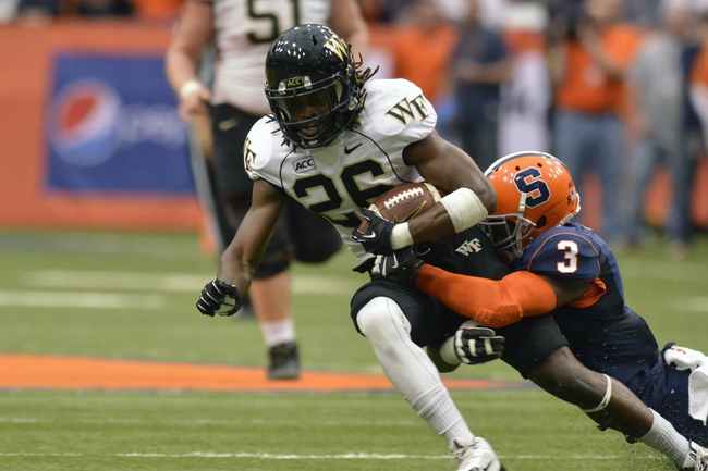 Nov 2, 2013; Syracuse, NY, USA; Wake Forest Demon Deacons wide receiver Sherman Ragland III (26) is tackled by Syracuse Orange safety Durell Eskridge (3) during the second quarter of a game at the Carrier Dome. Mandatory Credit: Syracuse won the game 13-0. Mark Konezny-USA TODAY Sports