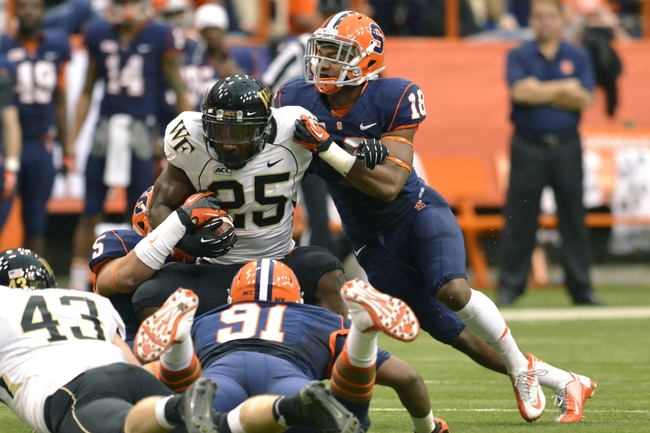 Nov 2, 2013; Syracuse, NY, USA; Wake Forest Demon Deacons running back Josh D. Harris (25) is tackled by Syracuse Orange defensive back Darius Kelly (18) during the second quarter of a game at the Carrier Dome. Mandatory Credit: Syracuse won the game 13-0. Mark Konezny-USA TODAY Sports