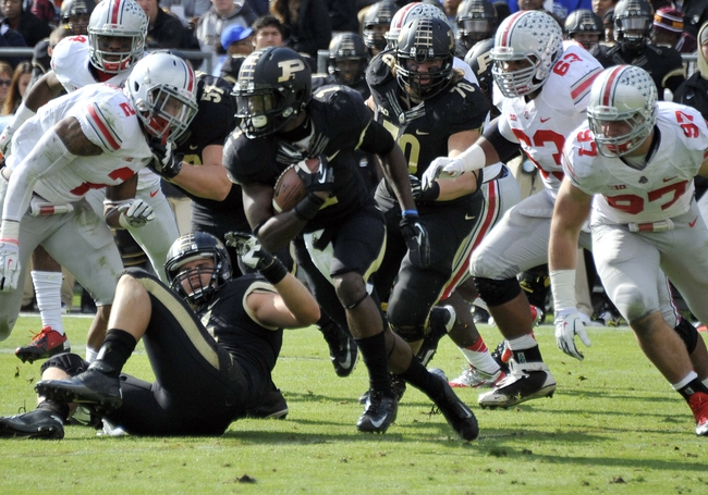 Nov 2, 2013; West Lafayette, IN, USA;  Purdue Boilermakers running back Akeem Hunt (1) runs past Ohio State Buckeyes defensive lineman Joey Bosa (97) and safety Christian Bryant (2) in the first half at Ross Ade Stadium. Mandatory Credit: Sandra Dukes-USA TODAY Sports