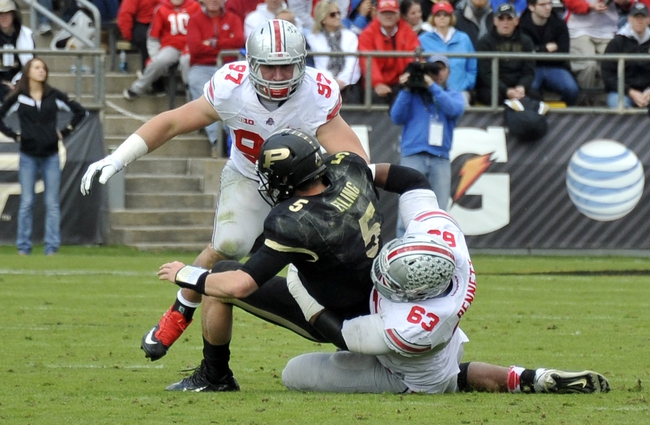 Nov 2, 2013; West Lafayette, IN, USA;  Purdue Boilermakers quarterback Danny Etling (5) is sacked by Ohio State Buckeyes defensive lineman Michael Bennett (63) and defensive lineman Joey Bosa (97) in the first half at Ross Ade Stadium. Mandatory Credit: Sandra Dukes-USA TODAY Sports