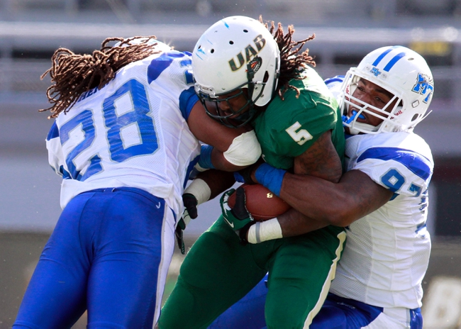 Nov 2, 2013; Birmingham, AL, USA;  Middle Tennessee State Blue Raiders linebacker Christian Henry (28) and defensive end Jiajuan Fennell (97) tackle UAB Blazers running back Darrin Reaves (5) at Legion Field. The Blue Raiders defeat the Blazers 24-21. Mandatory Credit: Marvin Gentry-USA TODAY Sports