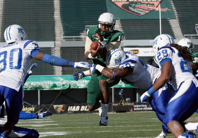Nov 2, 2013; Birmingham, AL, USA;  UAB Blazers quarterback Jonathan Perry (14) jumps over the goal line to score 2 points to tie the game and is hit by Middle Tennessee State Blue Raiders defensive end Jimmy Staten (90) at Legion Field. The Blue Raiders defeat the Blazers 24-21. Mandatory Credit: Marvin Gentry-USA TODAY Sports
