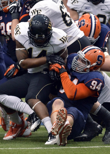 Nov 2, 2013; Syracuse, NY, USA; Wake Forest Demon Deacons running back Dominique Gibson (14) is tackled by Syracuse Orange defensive end Robert Welsh (94) in the third quarter of a game at the Carrier Dome. Syracuse won the game 13-0. Mandatory Credit: Mark Konezny-USA TODAY Sports