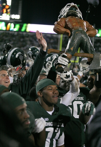 Nov 2, 2013; East Lansing, MI, USA; Michigan State Spartans defensive lineman Micajah Reynolds (60) raises the Paul Bunyan trophy after the game against the Michigan Wolverines at Spartan Stadium. Spartans beat the Wolverines 29-6. Mandatory Credit: Raj Mehta-USA TODAY Sports