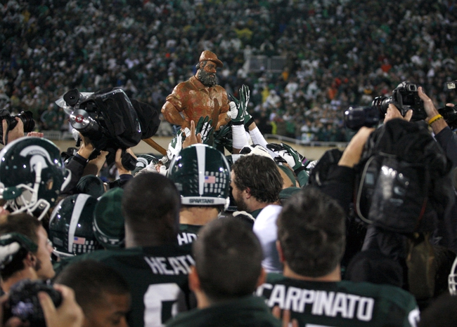 Nov 2, 2013; East Lansing, MI, USA; Michigan State Spartans raise the Paul Bunyan trophy after the game against the Michigan Wolverines at Spartan Stadium. Spartans beat the Wolverines 29-6. Mandatory Credit: Raj Mehta-USA TODAY Sports