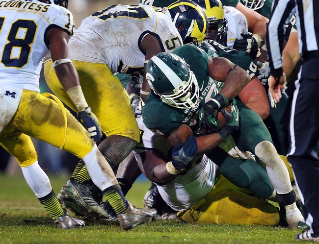 Nov 2, 2013; East Lansing, MI, USA; Michigan State Spartans running back Jeremy Langford (33) runs the ball against Michigan Wolverines defensive end Frank Clark (57) during the 2nd half of a game at Spartan Stadium. MSU won 29-6. Mandatory Credit: Mike Carter-USA TODAY Sports