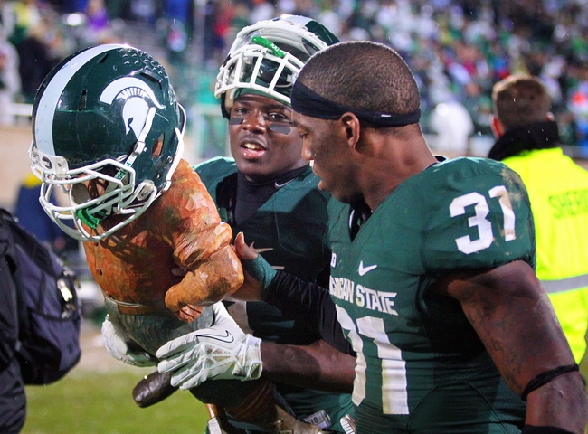 Nov 2, 2013; East Lansing, MI, USA; Michigan State Spartans safety Isaiah Lewis (9) and cornerback Darqueze Dennard (31) walk off the field with the Paul Bunyun trophy during the 2nd half of a game at Spartan Stadium. MSU won 29-6. Mandatory Credit: Mike Carter-USA TODAY Sports