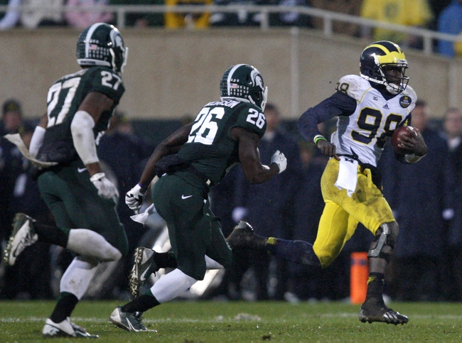 Nov 2, 2013; East Lansing, MI, USA; Michigan Wolverines quarterback Devin Gardner (98) gets chased by Michigan State Spartans safety RJ Williamson (26) during the fourth quarter at Spartan Stadium. Spartans beat the Wolverines 29-6. Mandatory Credit: Raj Mehta-USA TODAY Sports