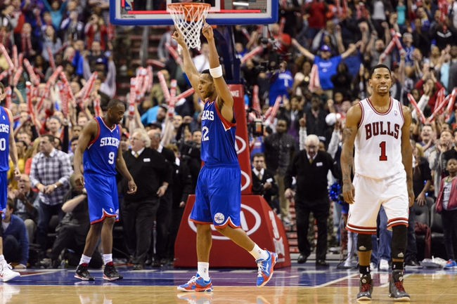 Nov 2, 2013; Philadelphia, PA, USA; Philadelphia 76ers guard Evan Turner (12) celebrates as Chicago Bulls guard Derrick Rose (1) walks off the court after the game. at Wells Fargo Center. The Sixers defeated the Bulls 107-104. Mandatory Credit: Howard Smith-USA TODAY Sports