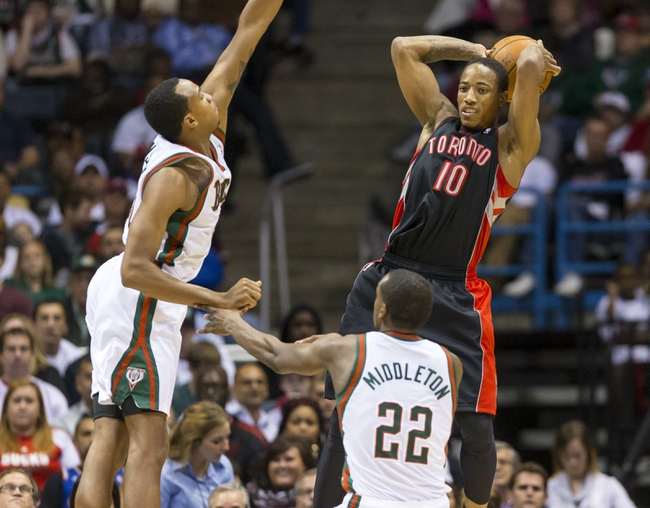 Nov 2, 2013; Milwaukee, WI, USA; Toronto Raptors guard DeMar DeRozan (10) passes the ball as Milwaukee Bucks forward John Henson (31) and forward Khris Middleton (22) defend during the third quarter at BMO Harris Bradley Center. Mandatory Credit: Jeff Hanisch-USA TODAY Sports