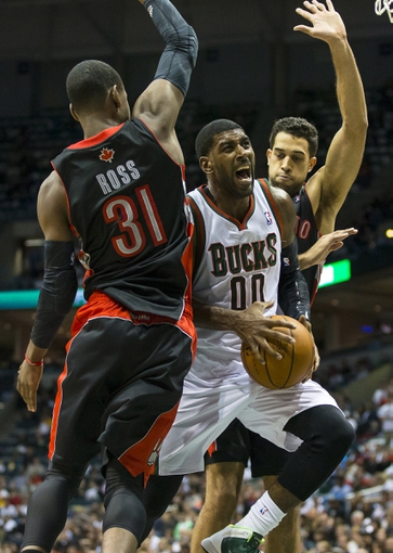 Nov 2, 2013; Milwaukee, WI, USA; Milwaukee Bucks guard O.J. Mayo (00) drives for a shot between Toronto Raptors guard Terrence Ross (31) and forward Landry Fields (2) during the third quarter at BMO Harris Bradley Center. Mandatory Credit: Jeff Hanisch-USA TODAY Sports