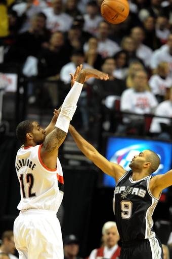 Nov 2, 2013; Portland, OR, USA; Portland Trail Blazers power forward LaMarcus Aldridge (12) shoots the ball over San Antonio Spurs point guard Tony Parker (9) during the first quarter of the game at  the Moda Center. Mandatory Credit: Steve Dykes-USA TODAY Sports