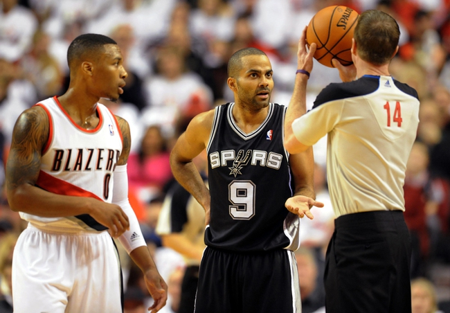Nov 2, 2013; Portland, OR, USA; Portland Trail Blazers point guard Damian Lillard (0) and San Antonio Spurs point guard Tony Parker (9) have some words with referee Ed Malloy (14) during the first quarter of the game at  the Moda Center. Mandatory Credit: Steve Dykes-USA TODAY Sports