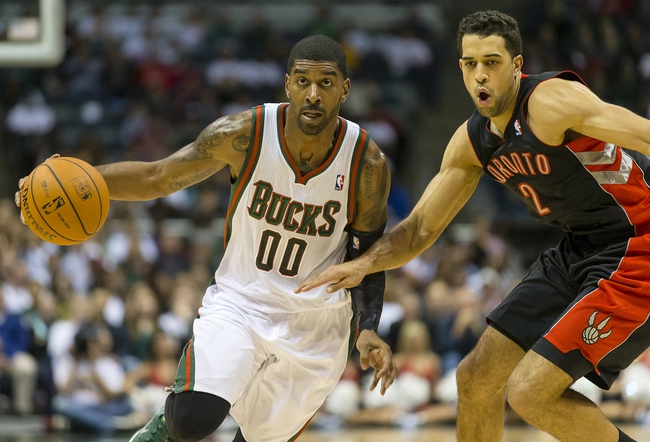 Nov 2, 2013; Milwaukee, WI, USA; Milwaukee Bucks guard O.J. Mayo (00) drives for the basket as Toronto Raptors forward Landry Fields (2) defends during the fourth quarter at BMO Harris Bradley Center. Toronto won 97-90.  Mandatory Credit: Jeff Hanisch-USA TODAY Sports