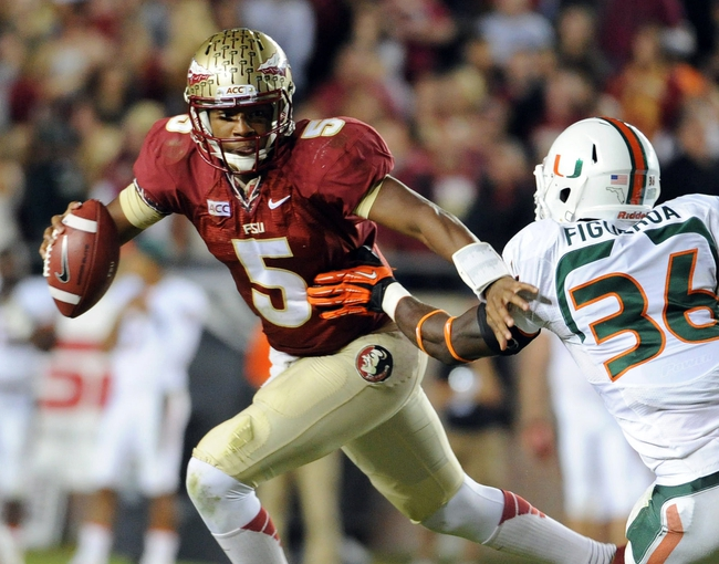 Nov 2, 2013; Tallahassee, FL, USA; Florida State Seminoles quarterback Jameis Winston (5) evades Miami Hurricanes linebacker Alex Figueroa (36) during the second half at Doak Campbell Stadium. Mandatory Credit: Melina Vastola-USA TODAY Sports